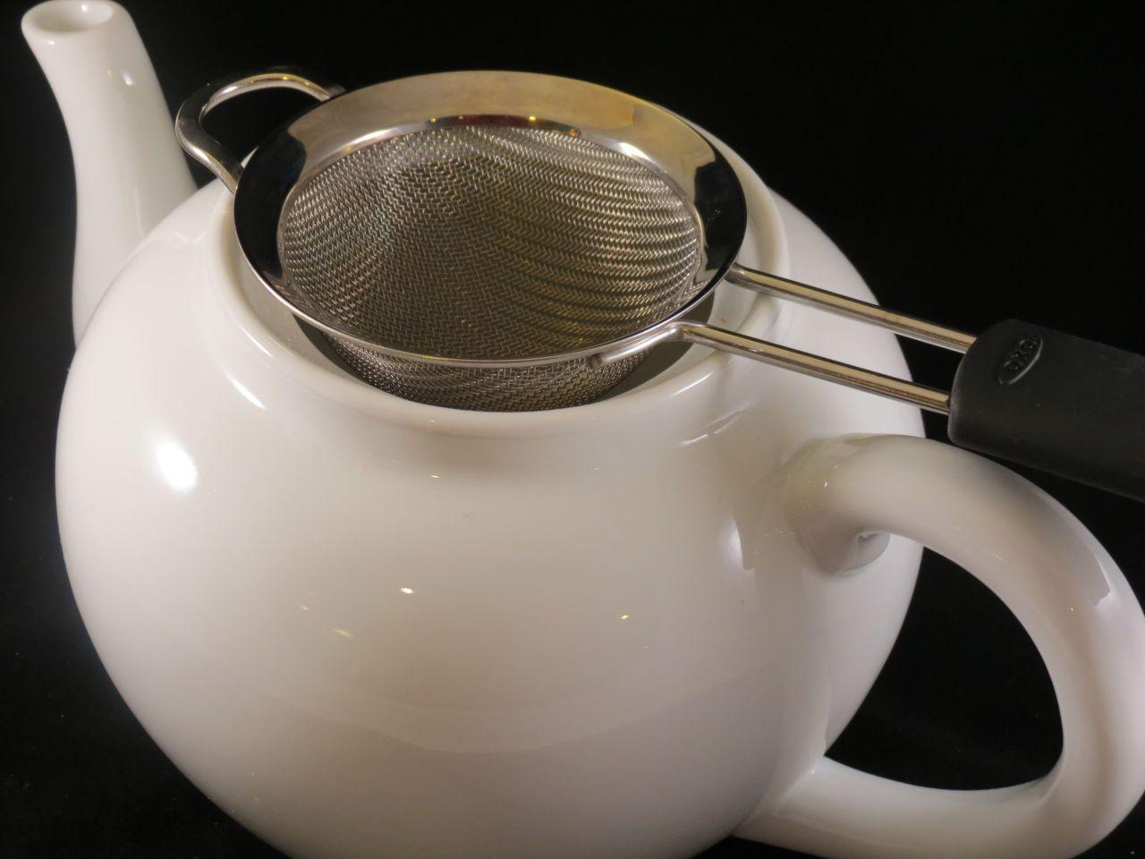 Masala Adrak Chai strain tea into a tea pot