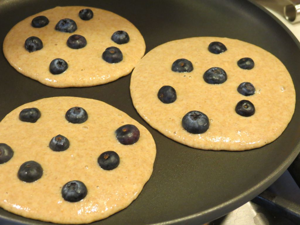 Blueberry Pancakes first pouring pancake batter and adding blueberries